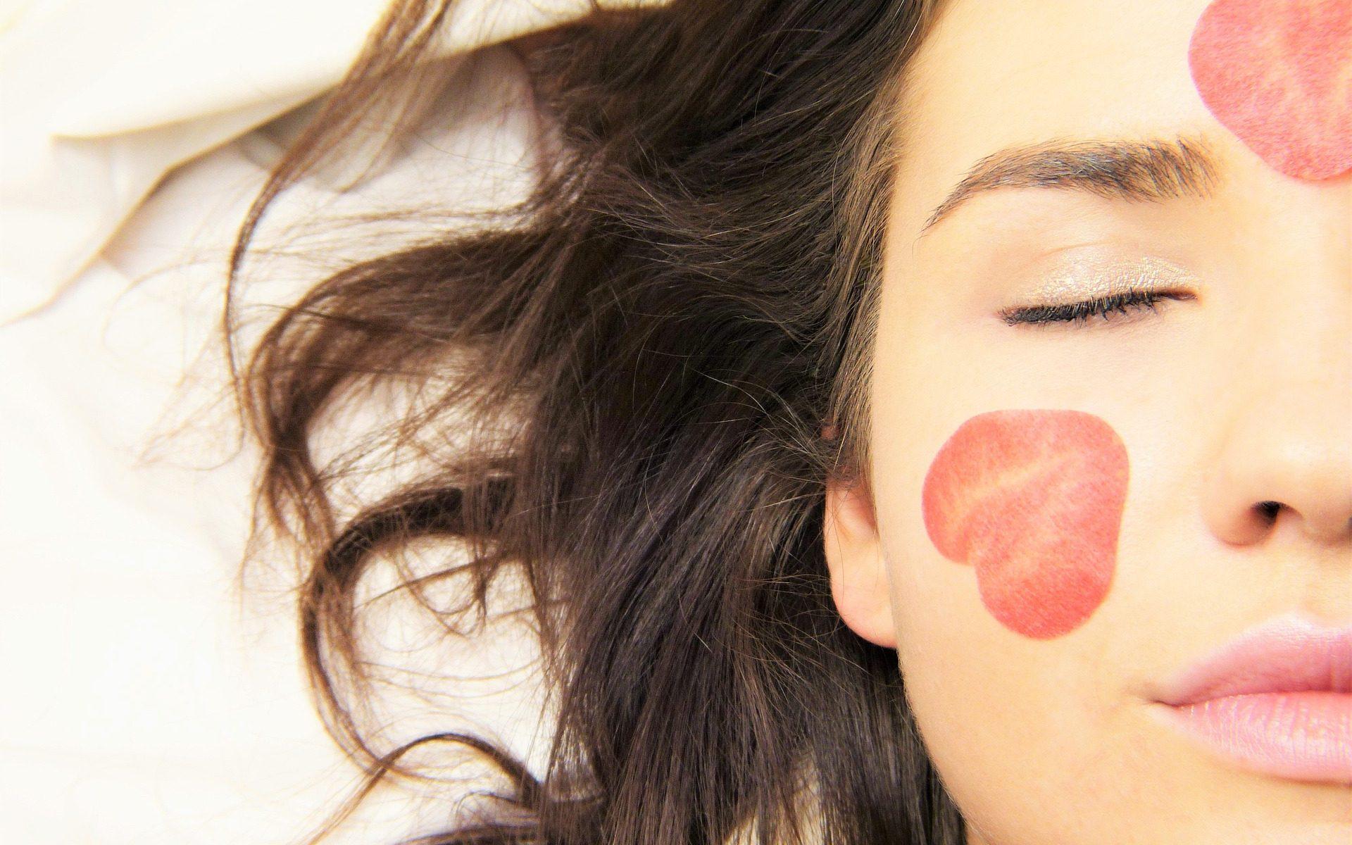 Une jeune fille avec des coeurs dessinés sur le visage et qui ferme les yeux comme si elle rêvait. Image choisie pour représenter le Projet associatif de Jeunes Pour le Monde
